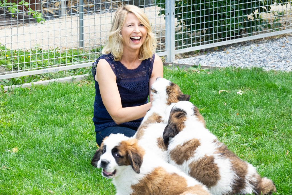 Samantha Brown playing with St. Bernard Puppies in Lake Geneva